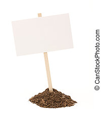Blank white sign in mound of dirt isolated on a white background.