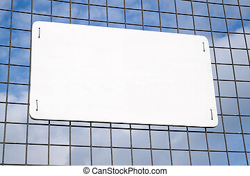 Blank white sign on a metal security fence.