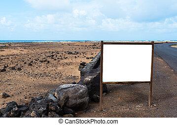 blank white sign post, billboard, information board, sign at roadside in deserted coastal landscape with ocean in background