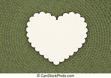 Blank wood heart on an olive green textured concentric circle fabric material