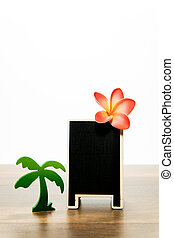 Blank wooden black board with Plumeria and Palm tree