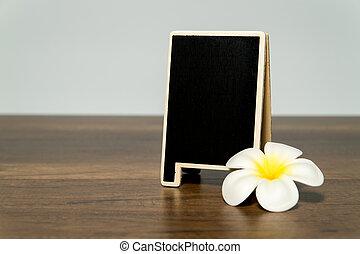 Blank wooden black board with white plumeria flower