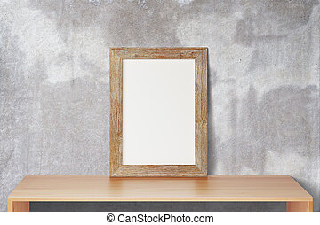 Blank wooden picture frame standing on the wooden table on a background of a concrete wall, mock up