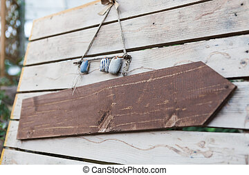 Blank wooden signboard hanging on a rope