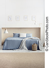 Blanket and cushions on blue bed in bright bedroom interior with carpet and posters. Real photo