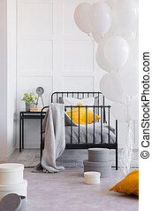 Blanket and orange pillow on bed next to table with plant in bedroom interior with balloons. Real photo
