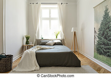 Blanket on black bed in bright bedroom interior with flowers, lamp and drapes at window. Real photo