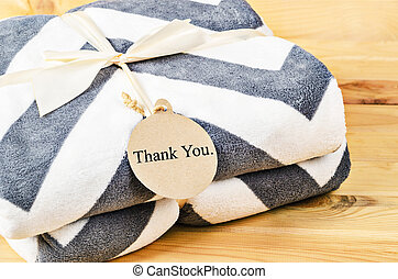 Blanket with Thank you tag gift with ribbon.