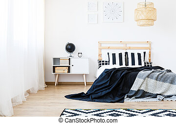 Blankets on bed - Black and white blankets on cozy wooden...