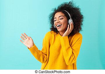 blaues, frau, mã¤nnerhemd, bezaubernd, aus, zuhören, freigestellt, gelber , radio, während, kopfhörer, musik, hintergrund, gebrauchend, spaß, amerikanische , singende, haben