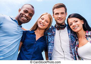 blaues, schauen, alles, guten, winkel , leute, wir, himmelsgewölbe, junger, vier, binden, fotoapperat, niedrig, hintergrund, friends., lächeln, ansicht, glücklich