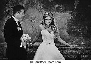 Blck and white picture of stunning bride leaning on old wall behind a groom