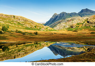 Landscape in Blea Tarn in the English Lake District with the Langdale Pikes in distance on sunny day.