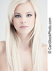 Young blond lady with a beautiful hair on gray background