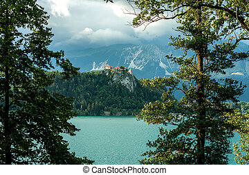 Bled castle between trees over the lake