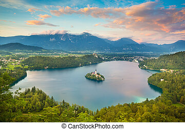 Sunset view of Julian Alps and Lake Bled with St. Marys Church of the Assumption on the small island. Bled, Slovenia, Europe.