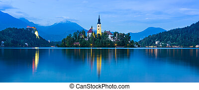 View of Julian Alps and Lake Bled with St. Marys Church of the Assumption on the small island at dusk. Bled, Slovenia, Europe.