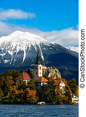 Bled lake with snow on the mountains in autumn
