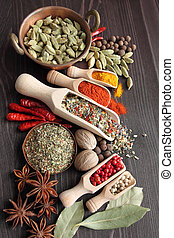 Colorful spices on wooden spoons and copper bowl - beautiful kitchen image.
