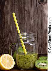 Blended green smoothie with kiwi and green apple on wooden background