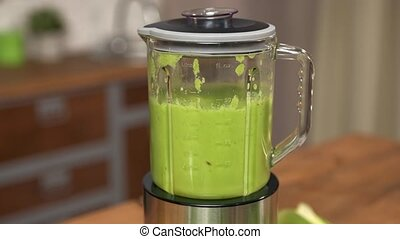 Blender Smoothie green colour macro view, cooking in slow motion