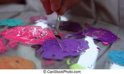 Blending of purple paint - An artist uses putty knife to mix...