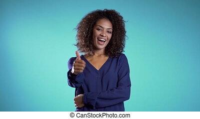 bleu, approval., girl, appareil photo, sourires, success., pouces, projection, geste, jeune, donne, africaine, positif, winner., femme affaires, haut., fond, lumière