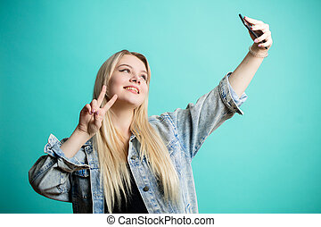 bleu, femme, positif, prendre, isolé, fond, amusement, confection, elle-même, selfie, blond-haired