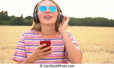 bleu, porter, femme, lunettes soleil, chemise, elle, téléphone, sans fil, écouteurs, écoute, jeune, cellule, champ, t-, musique, adolescent, joli, blond, rayé, girl