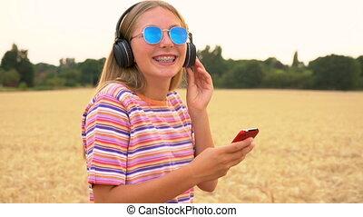 bleu, porter, marche, femme, lunettes soleil, chemise, elle, sans fil, écouteurs, écoute, jeune, téléphone portable, t-, musique, adolescent, joli, blond, rayé, girl