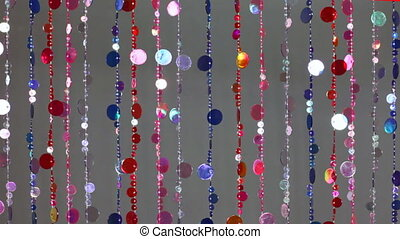 blind cords from of colorful beads flickering on gray...