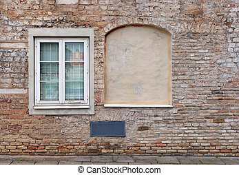 Blind curved basement windows in the old aged red bricks house.