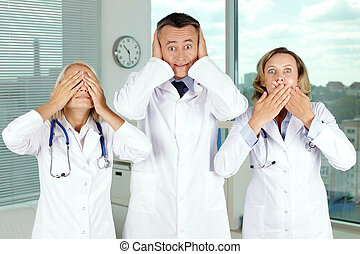 Blind, deaf, dumb - Three clinicians in white coats covering...