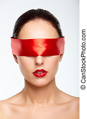 Gorgeous woman with red ribbon on her eyes over white background