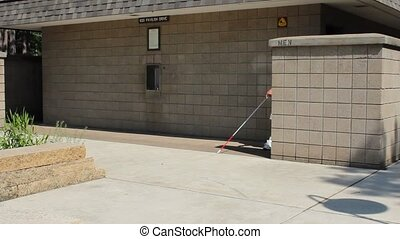 Blind man and cane - A blind man with his cane exits an...