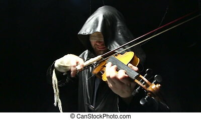Blind man playing on a fiddle, video on black background