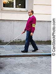 Blind man with stick - A blind man walks with a cane on a...