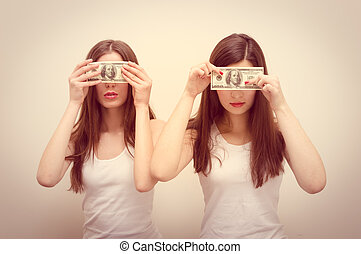 blind money concept: 2 beautiful girls young women wearing white shirts covering eyes with USD dollar banknote on white copy space background portrait