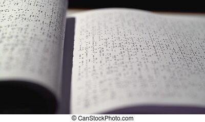 Blind with a braille font turning pages. Close up - Book for...