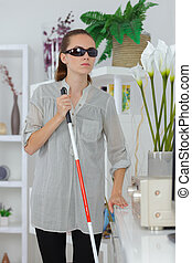 blind woman using stick to walk her way at home
