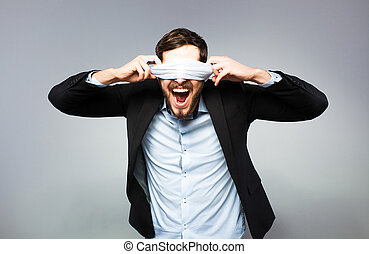 angry blindfolded man trying to unfold