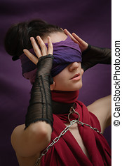 Blindfolded girl touches her head