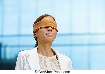 Blindfolded hispanic business woman near office building -...