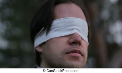 Blindfolded man in forest HD