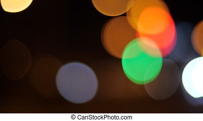 Blinking blurry lights in the dark. Circles of light flickered late at night. Various multi-colored glare of light blink in the dark. Abstract motion of light. Bright lights on a dark background.