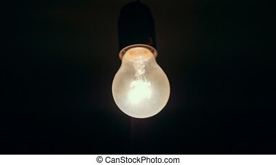 Blinking yellow lightbulb on the ceiling, close up