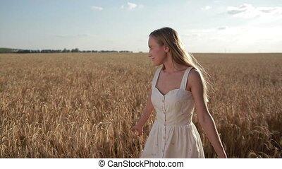 Blissful beautiful woman walking in cereal field