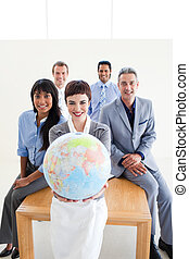 Blissful business team holding a terrestrial globe