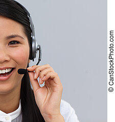 Blissful ethnic businesswoman using headset at work