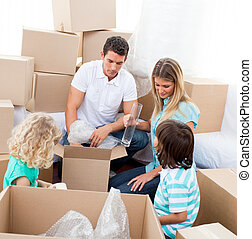 Blissful family packing boxes while moving house
